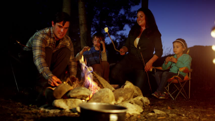 Happy American Caucasian family toasting smores in forest on vacation outdoor