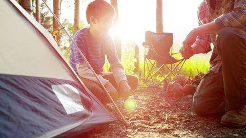 American Caucasian father and son erecting tent in forest on holiday outdoor