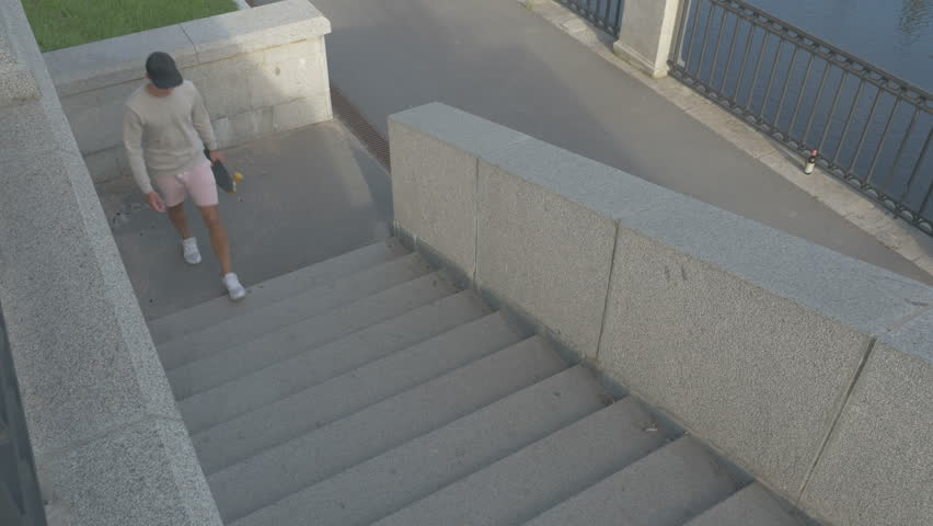 The skateboarder goes up the stairs on the street with a skateboard in hand. | Shutterstock HD Video #18307912