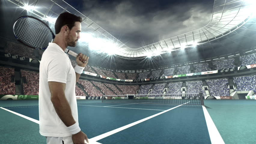 Tennis player tossing a ball in the air while holding his racquet in stadium