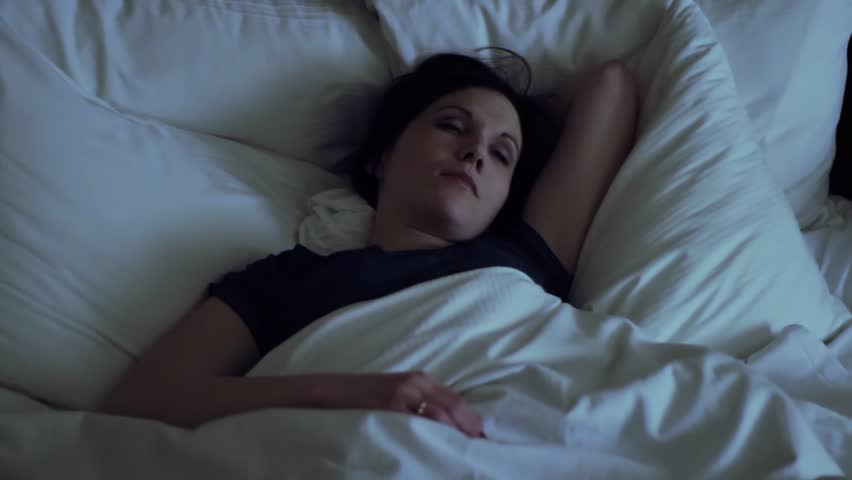 Woman has insomnia, tosses and turns in bed