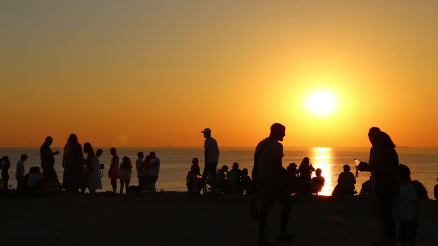 People silhouette watching sunset on the edge of the cliff at Bozcaada island, panning. | Shutterstock HD Video #18353812