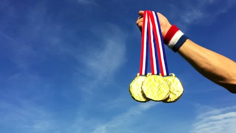 Hand of American athlete holding gold medals hanging from USA colors red, white, and blue ribbons against a blue sky background