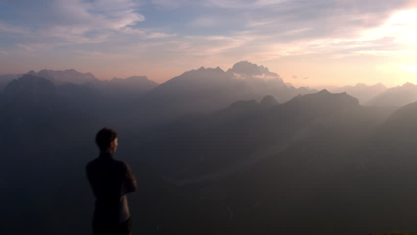 Aerial - Flyover hiker standing on top of the mountain and watching beautiful sunset after reaching the top