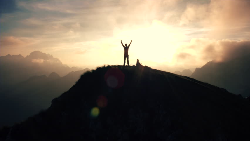 Aerial, edited - Moving above silhouette of a man standing on top of the mountain. Man raising arms victoriously after climbing the mountain