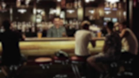 People sitting and relaxing at the bar, bartender clears the bar counter
