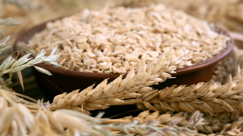 Diet food. Fresh oatmeal in a wooden plate. Wooden bowl rotates with spikelets of oats and oatmeal