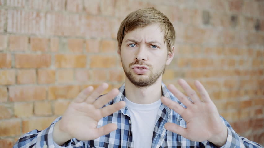 Portrait of Young Man Trying to Avoid Offer, Dislike, Rejecting Gesture, Disagree Sign
