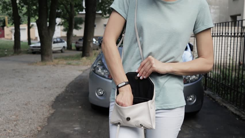 Woman looking for the car keys in her purse. In the background is the vehicle. | Shutterstock HD Video #18494362