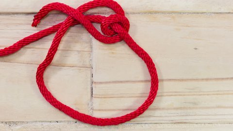 4k stop motion tarbuck knot made with red rope on wooden background.