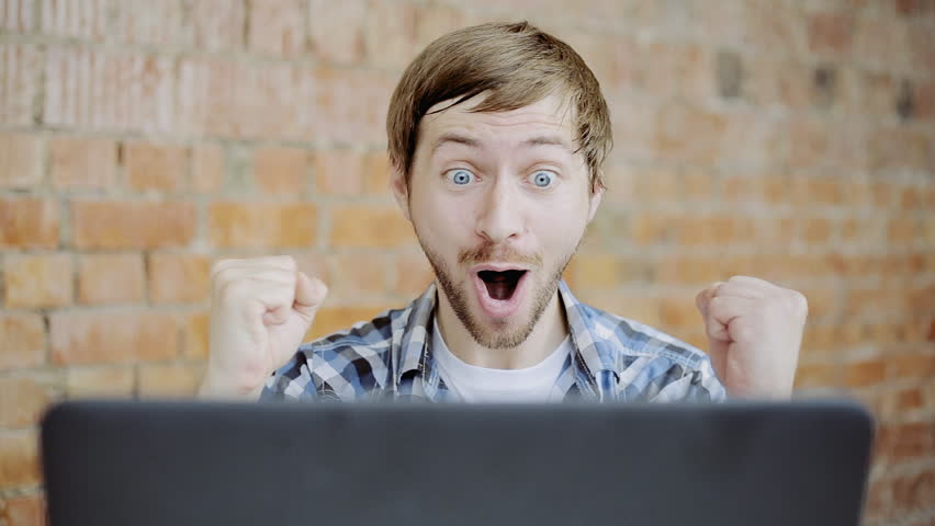 Young man very happy and rejoices sitting in front of laptop #18525092