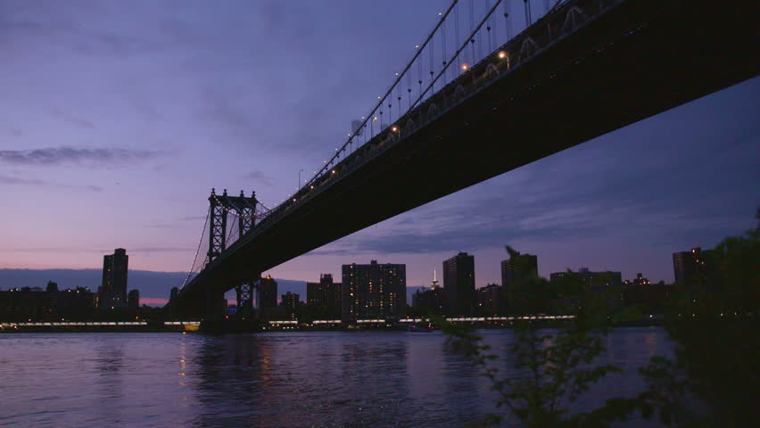 Manhatten bridge with the distinctive New York skyline in background at sunset, New York , United States