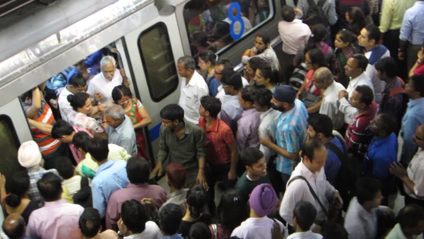 Crowds of people getting out a metro car in New Delhi