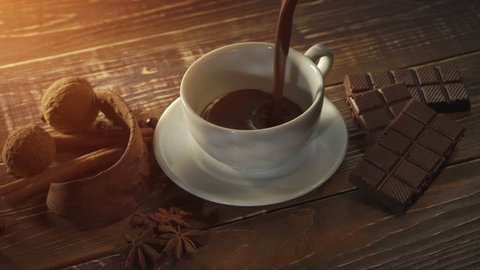 cup of hot chocolate, cinnamon sticks, nuts and chocolate bar on wooden table