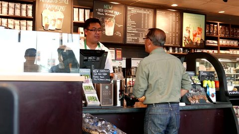 Coquitlam, BC, Canada - August 03, 2016 : Close up old man buying coffee and paying by cash inside Starbucks store with 4k resolution.