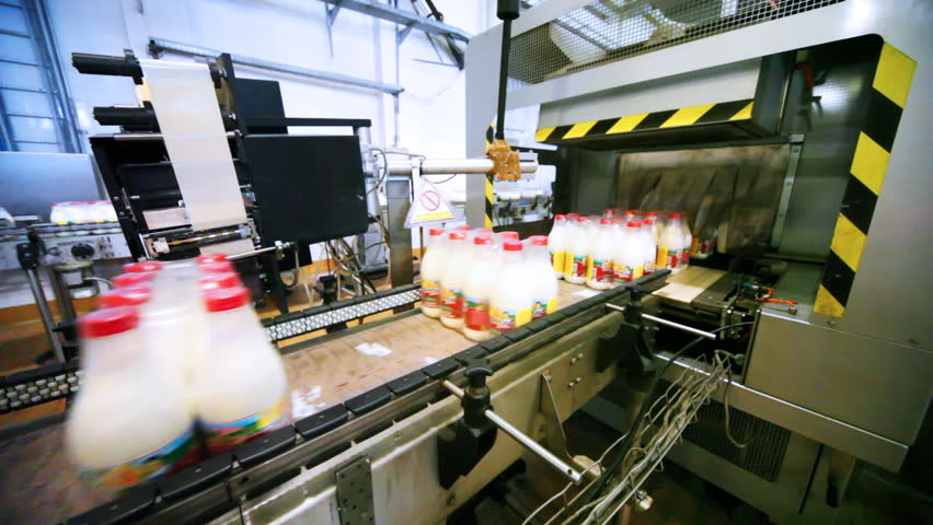 packets bottles of milk go belt conveyor and automation pastes to back side sticker