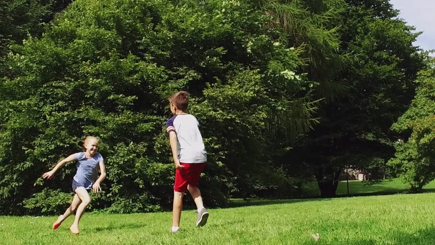 summer holidays, childhood, leisure and people concept - group of happy pre-teen kids playing tag game and running in park in slow motion mode