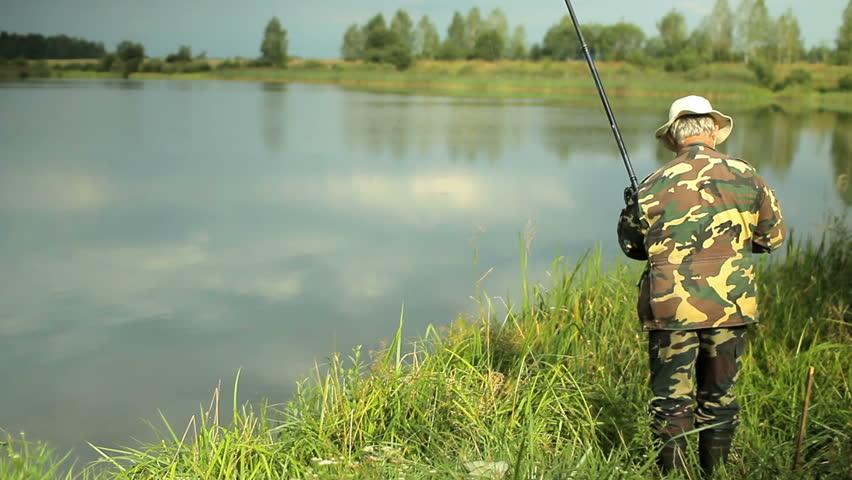 Hd0031fisher Man With Fishing Rod Catching Fish On Lake