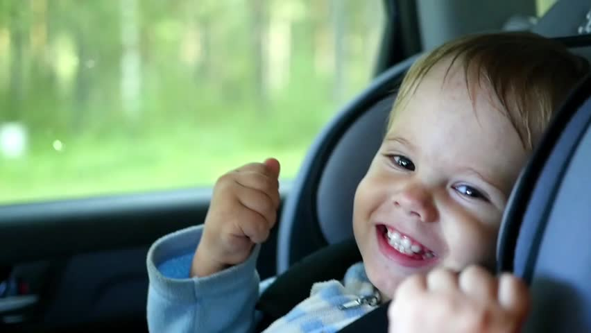 the child rides in the car and laughs