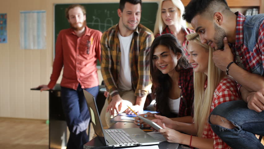 Students using tablet computer and laptop people group smile discussing sitting desk university classroom casual wear teacher | Shutterstock HD Video #18691862