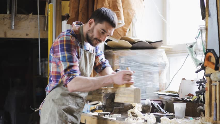 Profession, people, carpentry, woodwork and people concept - carpenter working with plane and wood plank at workshop   Shutterstock HD Video #18694679