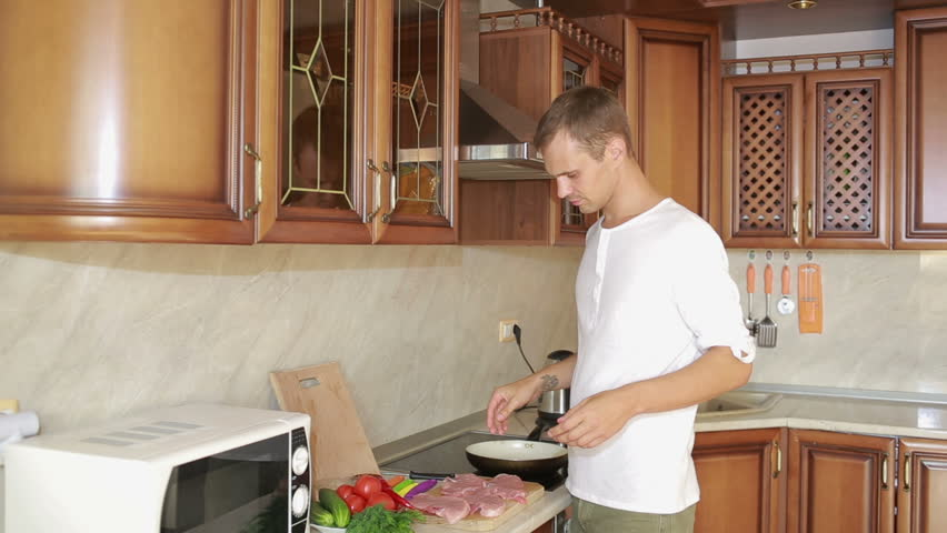 Young Man Cooking In The Kitchen. Man Preparing Meat   HD Stock Footage Clip