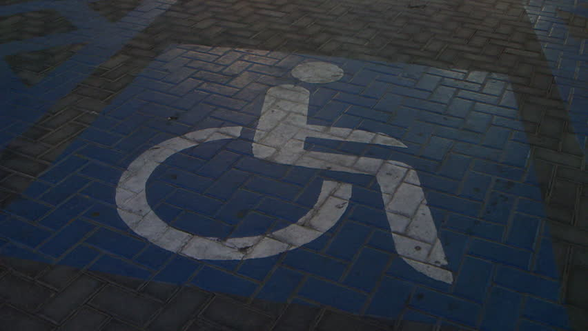 Disabled parking sign. High-angle view of a 'Disabled Parking Only' logo on the ground in a parking bay, in Abu Dhabi. (Abu Dhabi, UAE-2013)
