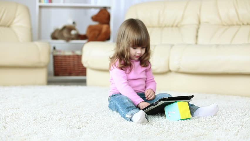 Baby girl holding a tablet and sits on the floor