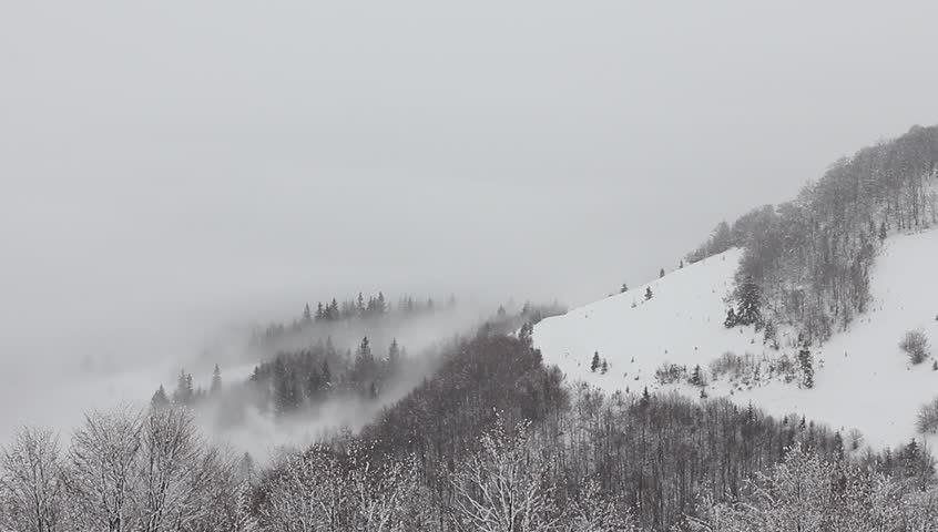 Falling snow in the mountains above the clouds