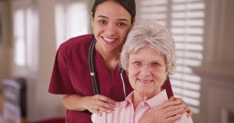Latina caretaker with senior woman smiling