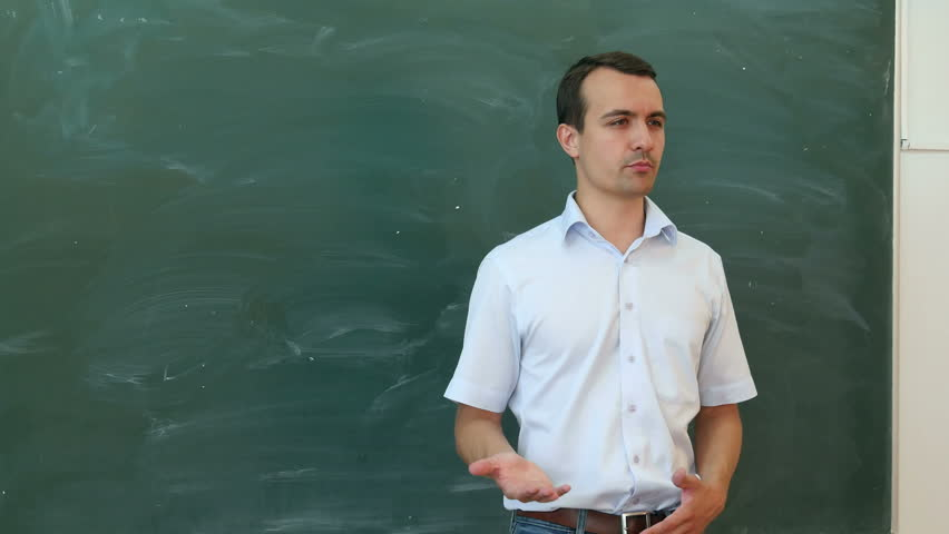 Young teacher or student tell something near the blackboard and gesticulate. | Shutterstock HD Video #18804272