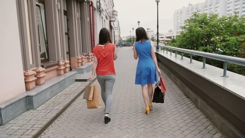 Two beautiful young woman friends walking with shopping bags, talking having fun, back view, slow mo steadicam shot #18809522