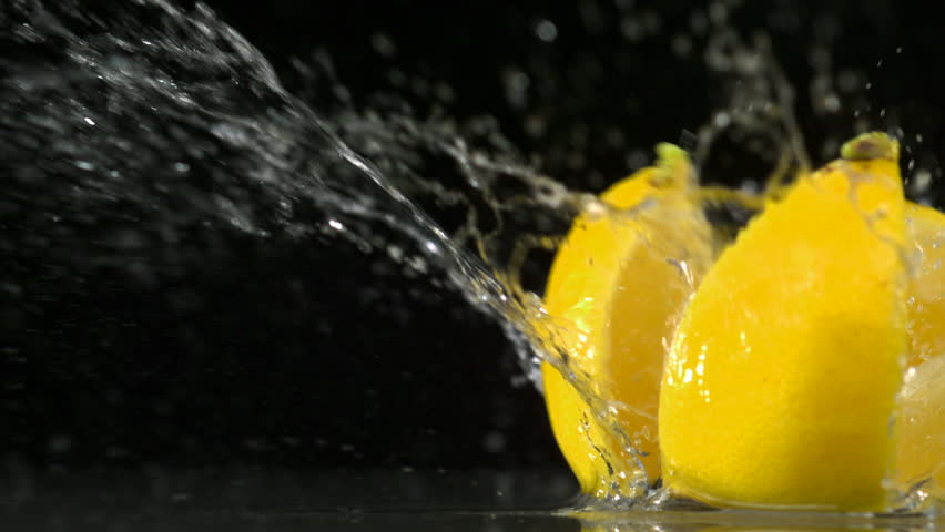 Slo-motion lemon  falling into wedges against black drop