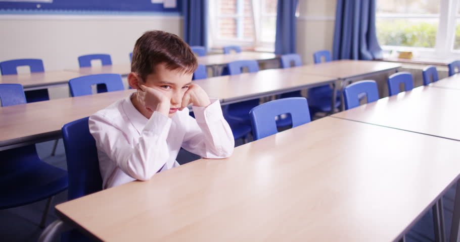 4k, Bored young student sitting alone in an empty class room during detention.