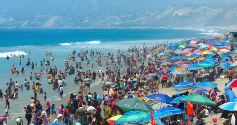 LOS ANGELES, CALIFORNIA, USA - JULY 26, 2016: Crowd of people swim in the Pacific Ocean in Santa Monica Beach on July 26, 2016 in Los Angeles, California, 4K, from RAW file, EDITORIAL