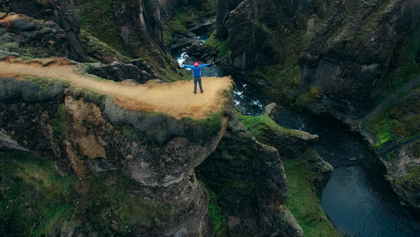 Aerial view of man with raised hands up feeling freedom while standing at Fjadrargljufur canyon in Iceland