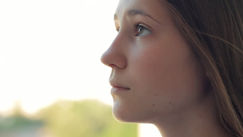 beautiful profile of a teen girl, she looks down, then up, day