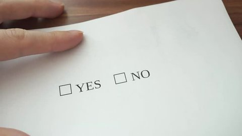 Hand is filling form with yes and no checkboxes, making decision and accepting it by writing check symbol on yes checkbox.