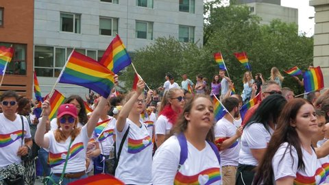 MONTREAL, CANADA - August 2016 : Young people waving the rainbow flag during the parade. Filmed During the 2016 annual LGBT gay pride parade festival in Montreal, Canada.