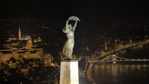 Aerial footage shows the Hungarian Liberty Statue overlooking the City of Budapest at night