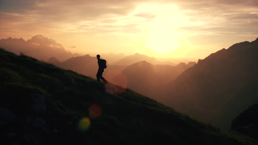 Aerial, edited - Epic shot of a man hiking on the edge of the mountain as a silhouette in beautiful sunset