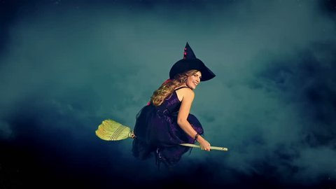Beautiful young witch flying on broom breaking through cloud mass. Halloween witch wearing witch hat.