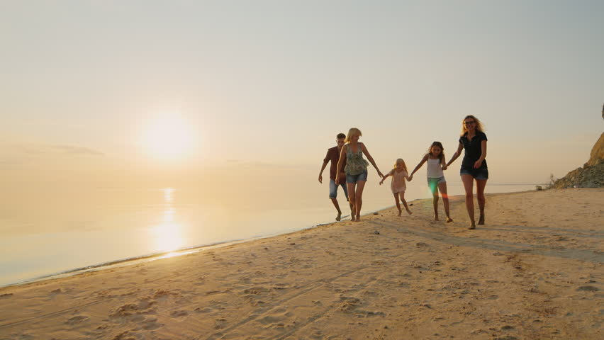 Group of carefree children of different ages and adults have fun running on the beach at sunset