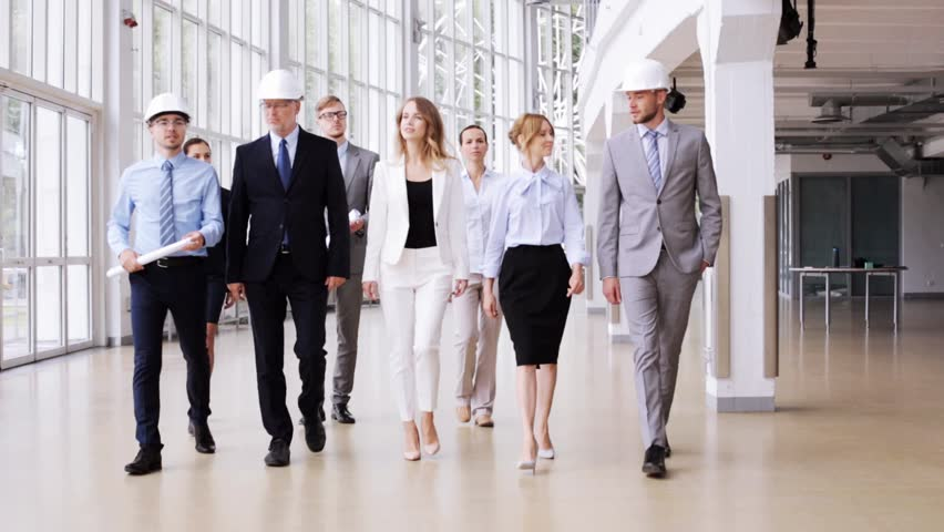 Business architecture construction teamwork and people concept business architecture construction teamwork and people concept happy group of architects in helmets with blueprint walking along at office building malvernweather Gallery
