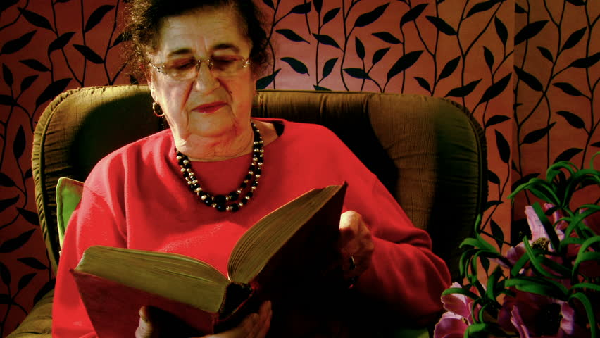 Elderly woman reads the book