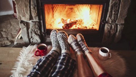 Couple Feet in Woollen Socks by the Cozy Fireplace, 4K. Man and Woman relax by warm fire and warming up their feet. Close up. Winter and Christmas holidays concept.