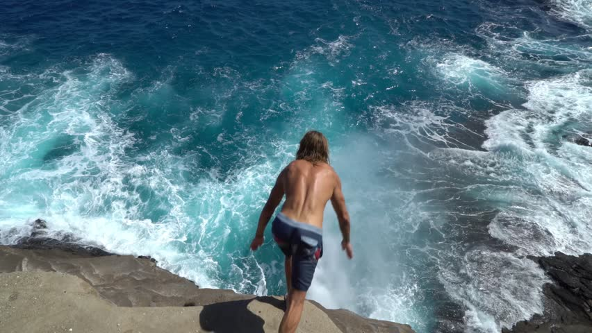 Male athlete jumping from a cliff into the water, Hawaii