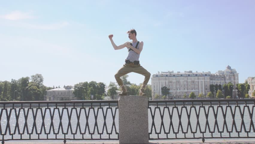 Man in marine shirt, military pants dance electro, staying on postament at seafront. Surrealism. Water, summer sunny day | Shutterstock HD Video #19050532