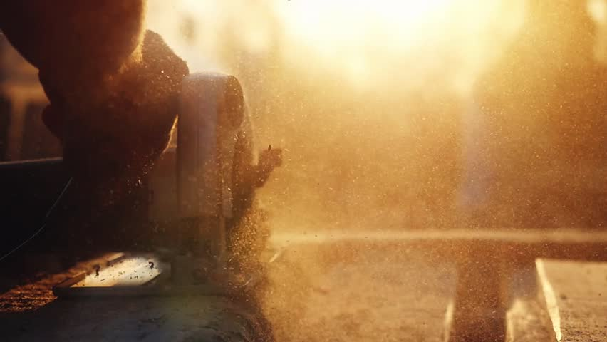Man is craft working at a work bench with power tools in slowmotion during sunset with beautiful lens flare. 1920x1080 | Shutterstock HD Video #19061482