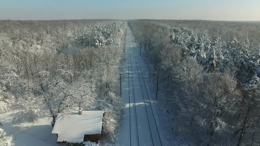 4K drone shot of a railway passing through the forest in winter